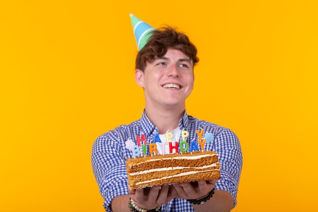 Fou joyeux jeune homme en papier chapeau de félicitations tenant des gâteaux joyeux anniversaire debout sur un mur jaune. concept de félicitations du jubilé.