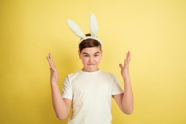 Fou pointant vers le haut. garçon de race blanche comme un lapin de pâques sur fond de studio jaune. bonnes salutations de pâques. beau modèle masculin. concept d'émotions humaines, expression faciale, vacances. copyspace.