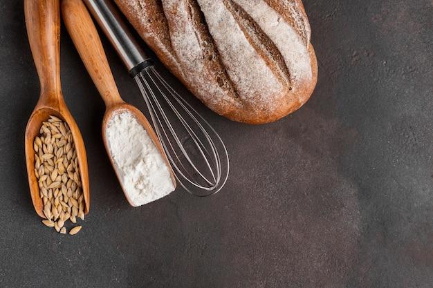 Fouet et cuillères en bois avec farine et graines