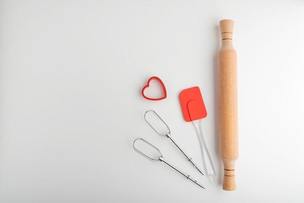 Fouet mélangeur, spatule en silicone de cuisine, rouleau à pâtisserie et emporte-pièce sur fond blanc.