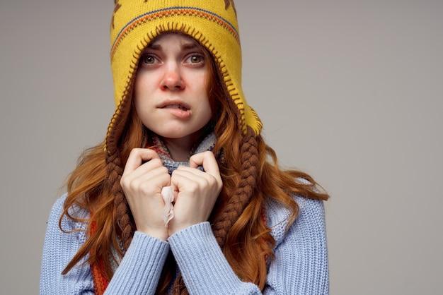 Foulard de femme aux cheveux roux avec un chapeau sur sa tête fond clair. photo de haute qualité