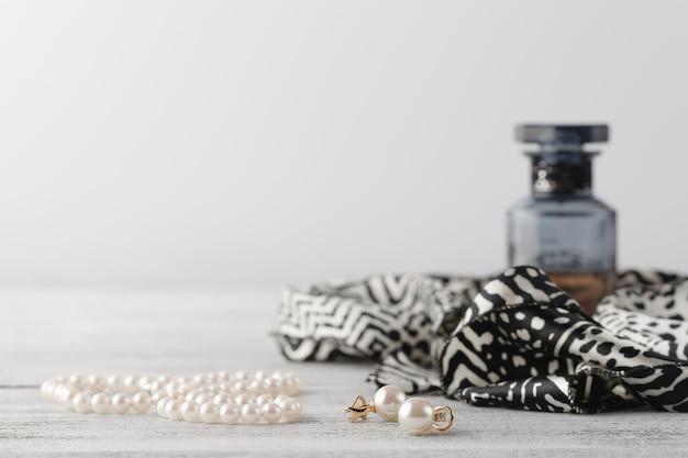 Foulard femme sur table avec parfum et bijouterie de perles