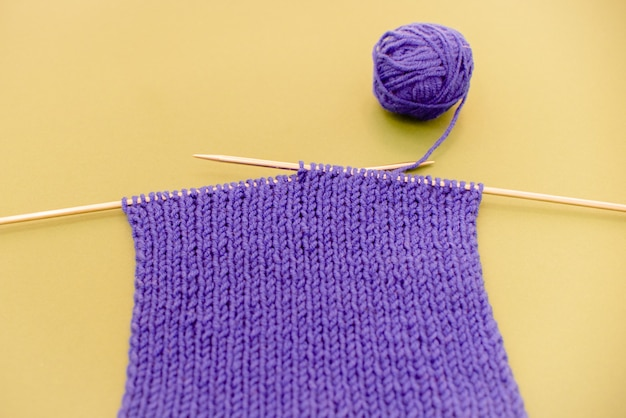Foulard tricoté avec des aiguilles à tricoter sur fond jaune.