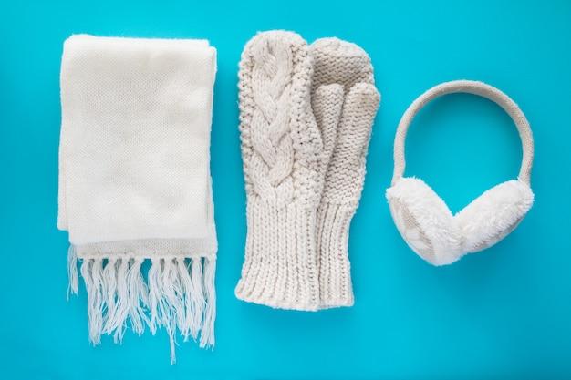 Foulard tricoté confortable, mitaines, écouteurs chauds sur fond bleu.