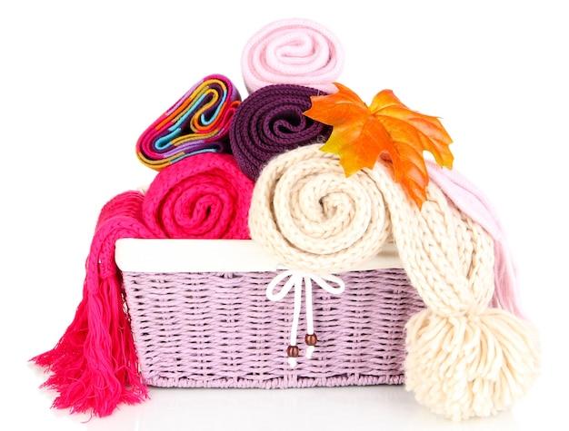 Foulards tricotés chauds dans le panier isolé sur blanc