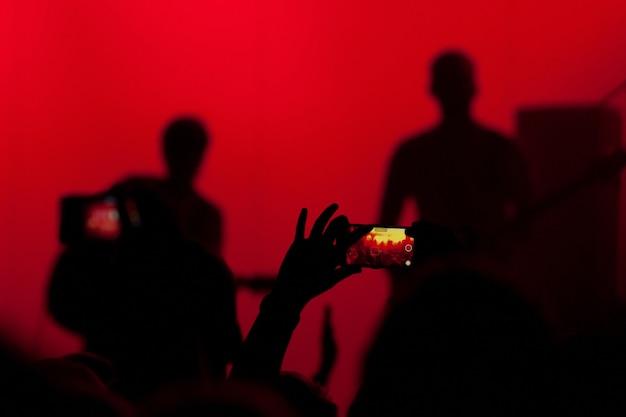La foule du concert prend une vidéo et une photo du concert au téléphone