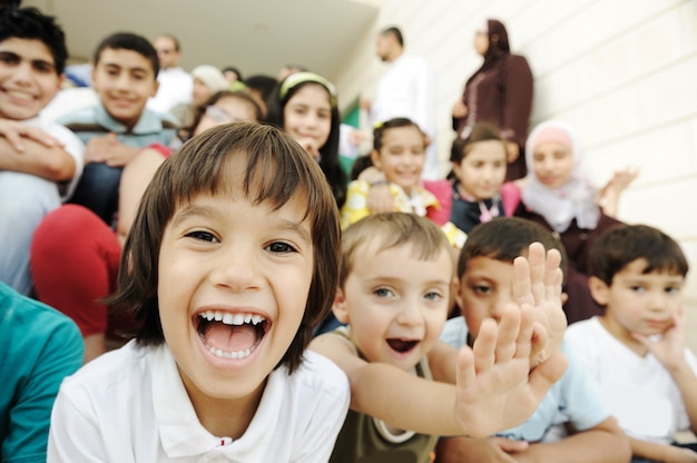 Foule d'enfants, différents âges et races devant l'école, pause