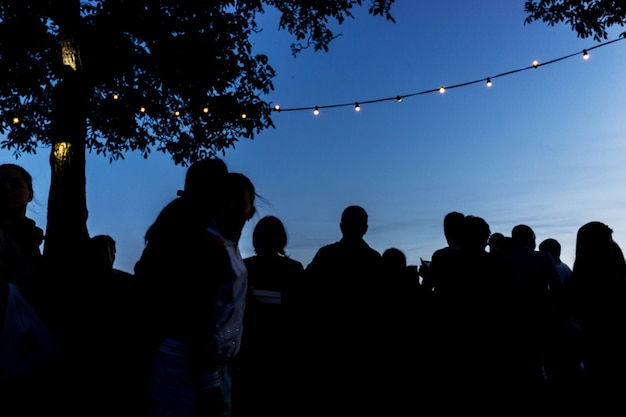 Foule les gens ensemble en plein air en attendant le coucher du soleil