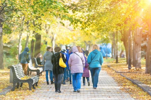 Foule de gens marchant dans le parc de la ville d'automne
