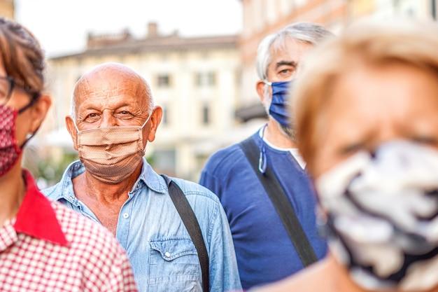 Foule de gens marchant dans les rues de la ville avec un masque facial