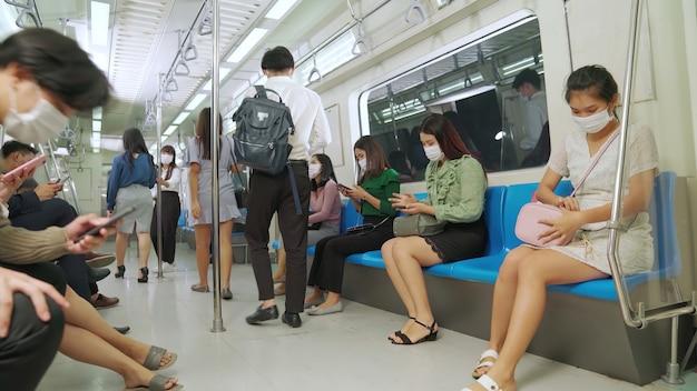 Foule de gens portant un masque facial sur un voyage en métro public bondé