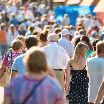 Foule de gens avec un vieil homme au centre marchant dans la rue animée de la ville