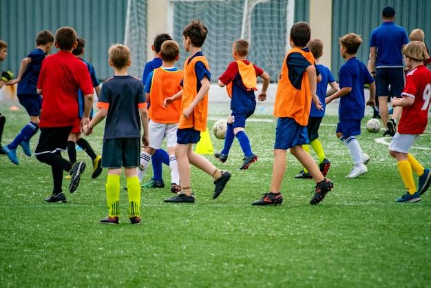 Foule de nombreux enfants jouant au football sur le terrain en herbe des stades