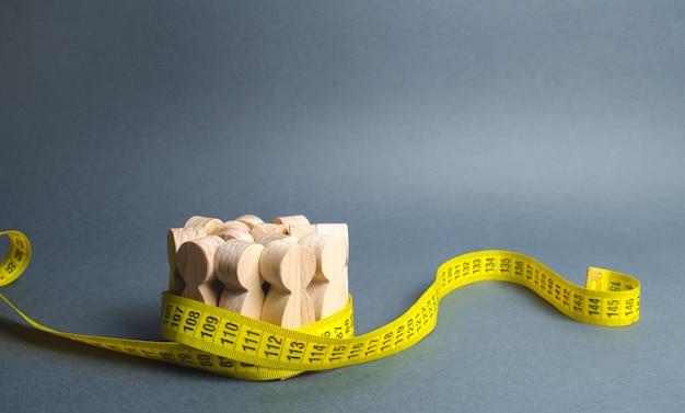 Une foule de personnages en bois saisis par un ruban à mesurer.