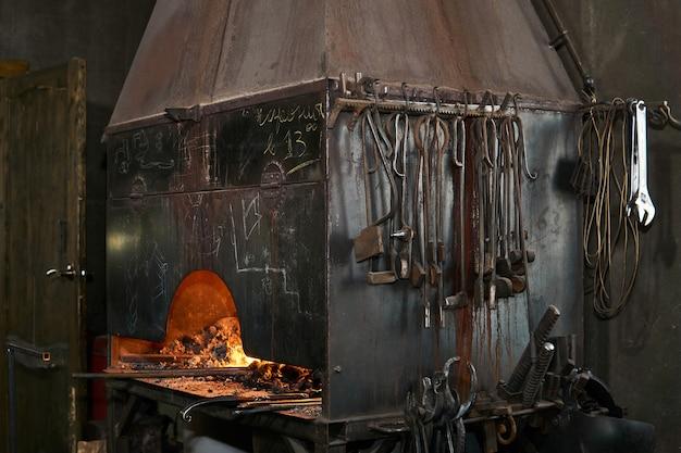 Four de forge avec flamme brûlante et outils de forgeron