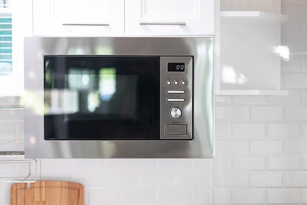 Le four à micro-ondes flotte et pend sous l'armoire sur le mur de la cuisine.