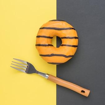 Une fourchette et un beignet glacé sur fond jaune et noir. une collation sucrée populaire.