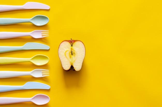 Fourchette colorée, cuillère et couteau avec pomme de coupe sur fond jaune avec un espace vide pour le texte.