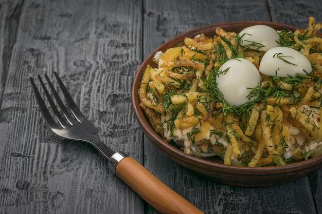 Une fourchette à côté d'un bol de salade aux œufs de caille