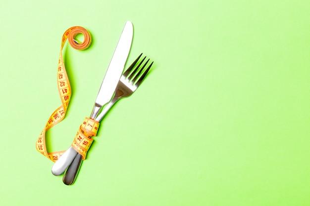 Fourchette et couteau enveloppés dans du ruban à mesurer