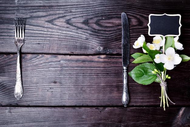 Fourchette et couteau en fer avec un bouquet de jasmin