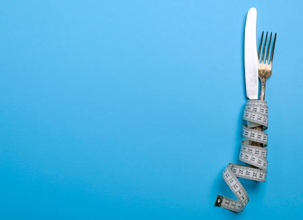 Fourchette et couteau en fer enveloppés dans un ruban à mesurer