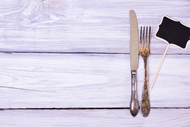 Fourchette et couteau en fer sur une surface en bois blanche