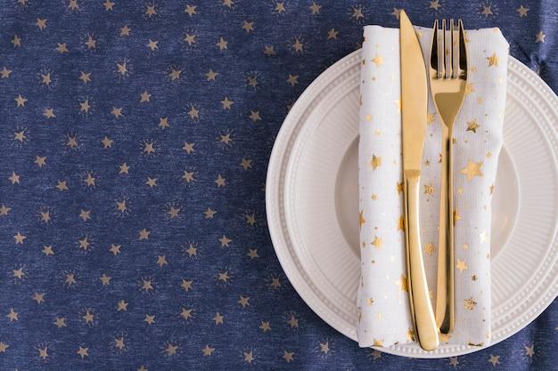 Fourchette et couteau en or sur assiette