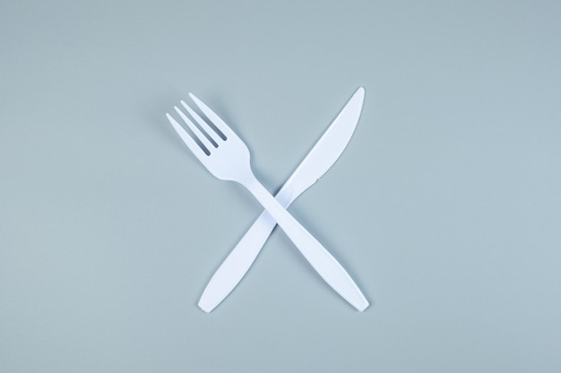 Fourchette et couteau en plastique blanc sur gris avec espace de copie pour le texte. protection de l'environnement, zéro déchet, réutilisable, ne dites pas de plastique, concept de la journée mondiale de l'environnement et du jour de la terre