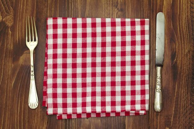 Fourchette avec couteau et serviette sur une table en bois marron
