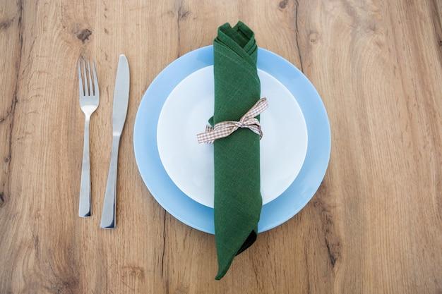 Fourchette, couteau, serviette verte avec assiette