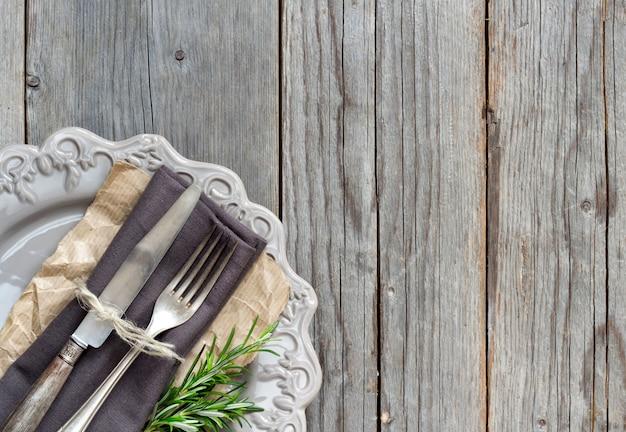 Fourchette et couteau vintage sur une serviette grise sur une plaque avec du romarin frais sur la table en bois vue de dessus avec copie espace