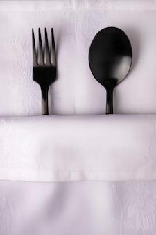 Une fourchette et une cuillère noires sur une serviette blanche. ils symbolisent un couple amoureux dans un lit sous une couverture blanche. le sexe et les relations, le concept du restaurant, la saint-valentin,
