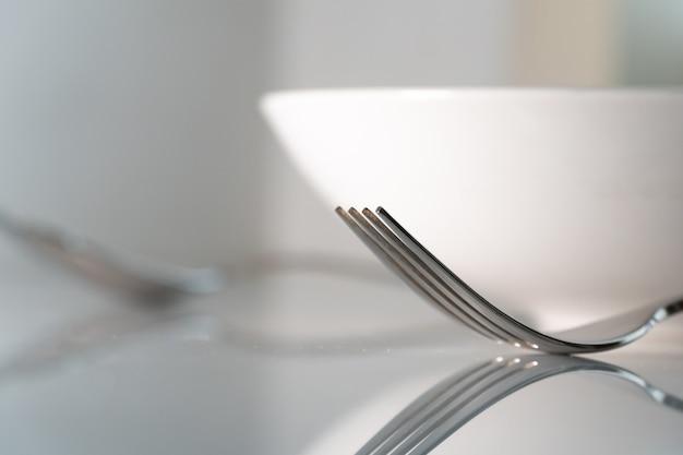 Fourchette et cuillère avec plat blanc sur fond de texture de marbre blanc. concept pour la vaisselle et la table à manger