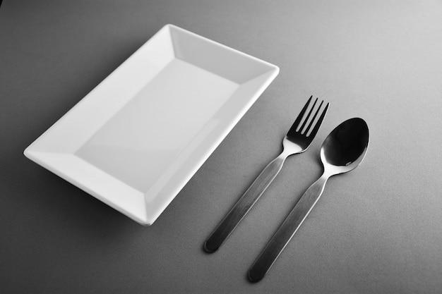 Fourchette, cuillère et un plat carré en céramique blanche