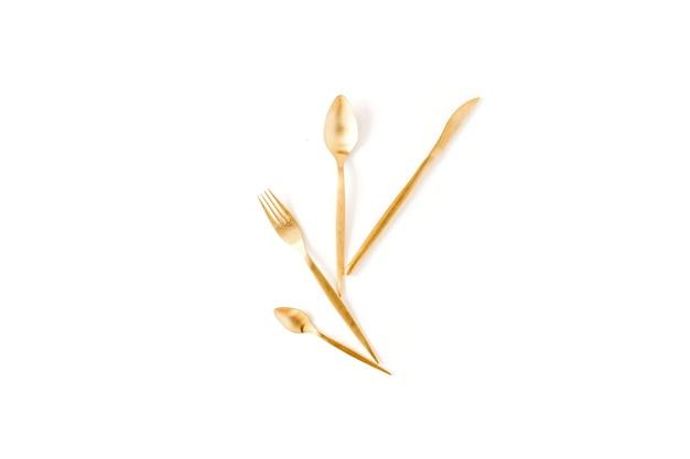 Fourchette d'or, cuillère, couteau isolé sur blanc