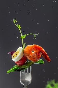 Fourchette avec salade de légumes isolés sur noir. crevettes fumées et salade de légumes frais et oeuf. éclaboussures de jus de citron.