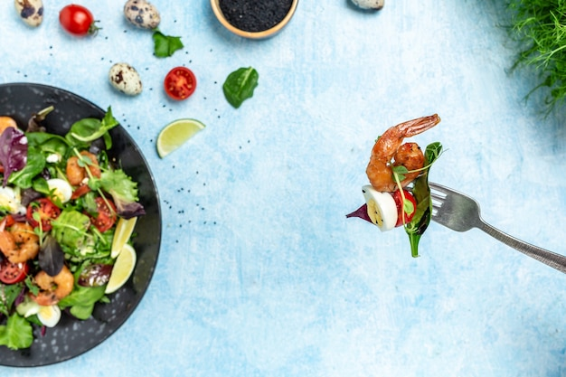 Fourchette avec salade de légumes tomates cerises, concombre, avocat, œufs et crevettes fumées. délicieux petit-déjeuner ou collation sur fond bleu, vue de dessus.