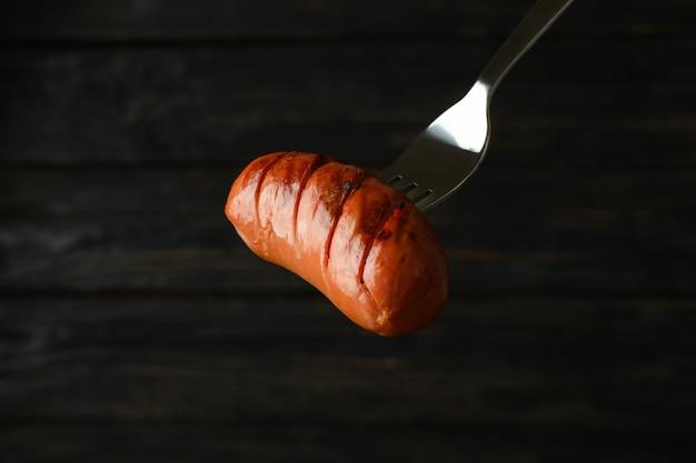 Fourchette avec saucisse grillée sur une surface en bois