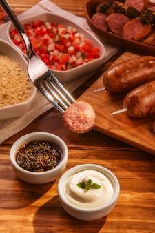 Fourchette servant saucisse de porc grillée avec chimichurri