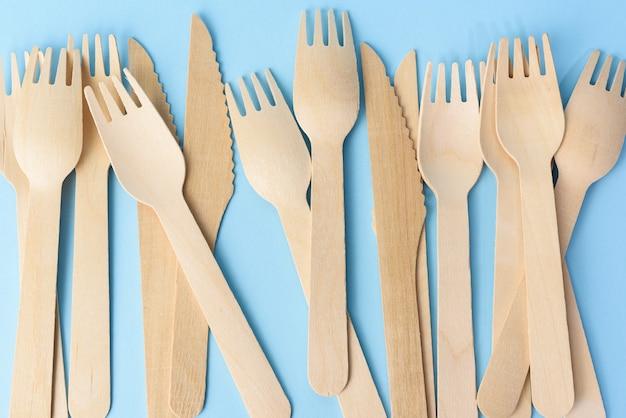 Fourchettes et couteaux en bois sur fond bleu, zéro déchet