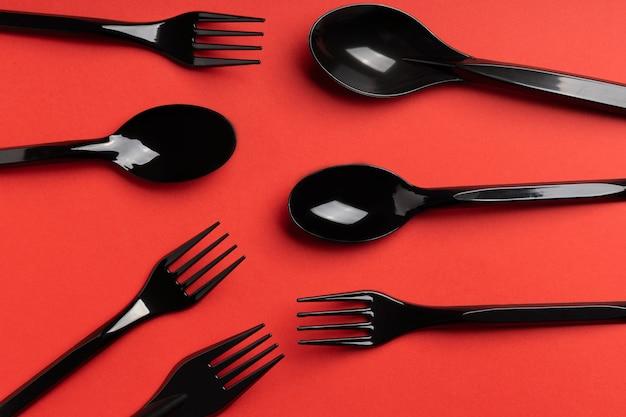 Fourchettes, cuillères et couteaux sur fond rose. couverts en plastique, écologie, pollution de l'environnement par le plastique, vaisselle jetable, concept de recyclage des déchets. modèle, mise à plat