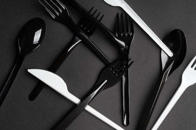 Fourchettes et cuillères sur fond gris. couverts en plastique, écologie, pollution de l'environnement par le plastique, vaisselle jetable, concept de recyclage des déchets. copyspace, mise à plat.