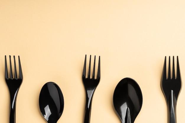 Fourchettes et cuillères sur fond jaune. couverts en plastique, écologie, pollution de l'environnement par le plastique, vaisselle jetable, concept de recyclage des déchets. copyspace, lieu de texte.