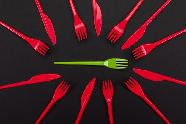 Fourchettes en plastique jetables rouges et verts isolés sur fond
