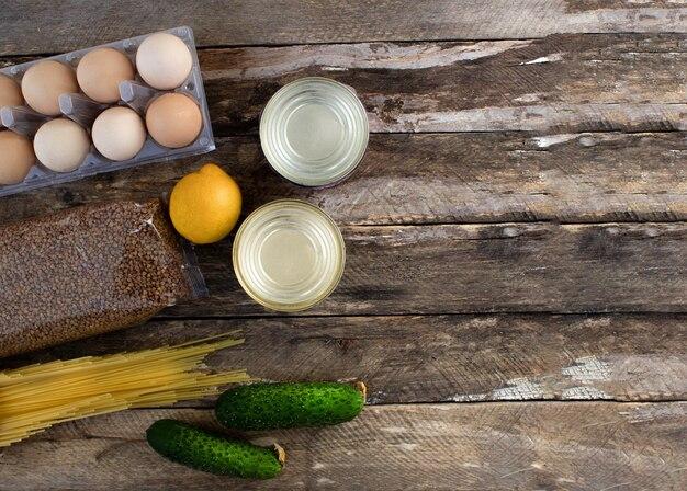 Fournitures alimentaires l'achat de nourriture sur un fond en bois oeufs en conserve de légumes pâtes alimentaires sur un fond en bois