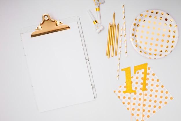 Fournitures anniversaire jaunes à côté du presse-papier blanc