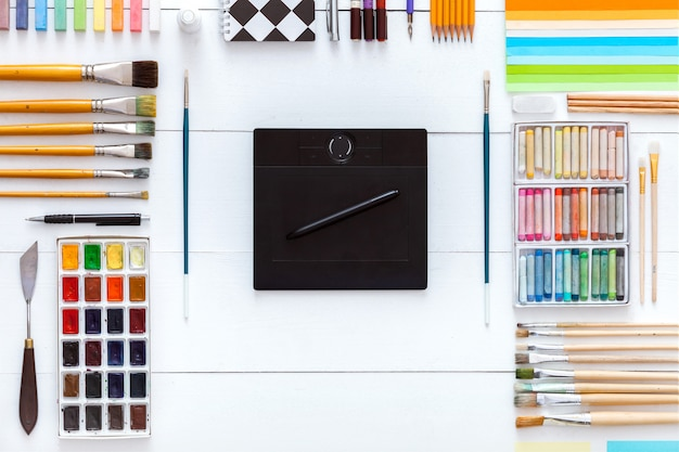 Fournitures et appareils pour le concept de travail d'art créatif, ensemble de fournitures et tablette wacom numérique sur fond en bois blanc, pinceaux