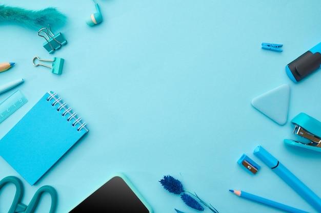 Fournitures de bureau dans les tons bleus. accessoires scolaires ou éducatifs, outils d'écriture et de dessin, crayons et stylos, clips et bloc-notes