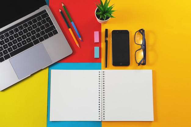 Fournitures de bureau sur un fond coloré, vue de dessus.